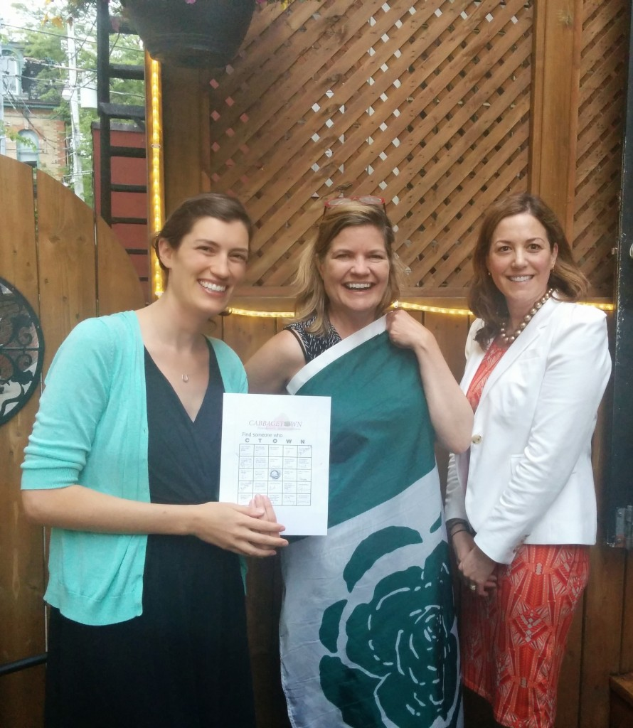 Winner of the Cabbagetown Bingo Game, Kelley Teahen shows off her prize Cabbagetown flag, bookended by Board Member Lindsay Whitfield and Board Secretary Carolyn Shaw-Rimmington.